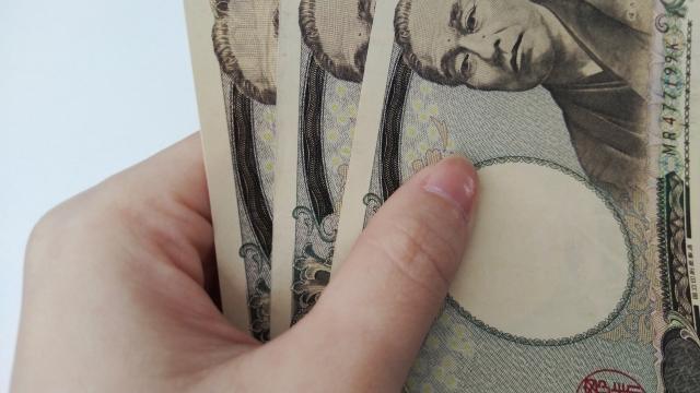 1万円札を持つ女性の手