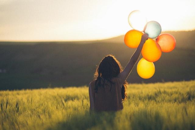 草原で風船を持つ女性