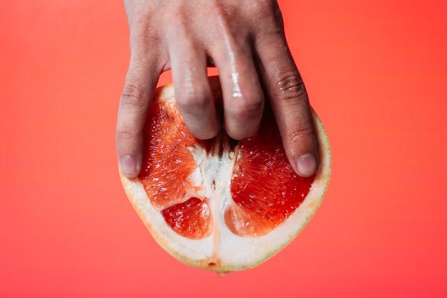 グレープフルーツに指を入れる男性