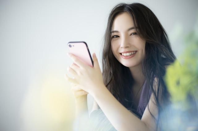 スマホを持つ笑顔の美人女性