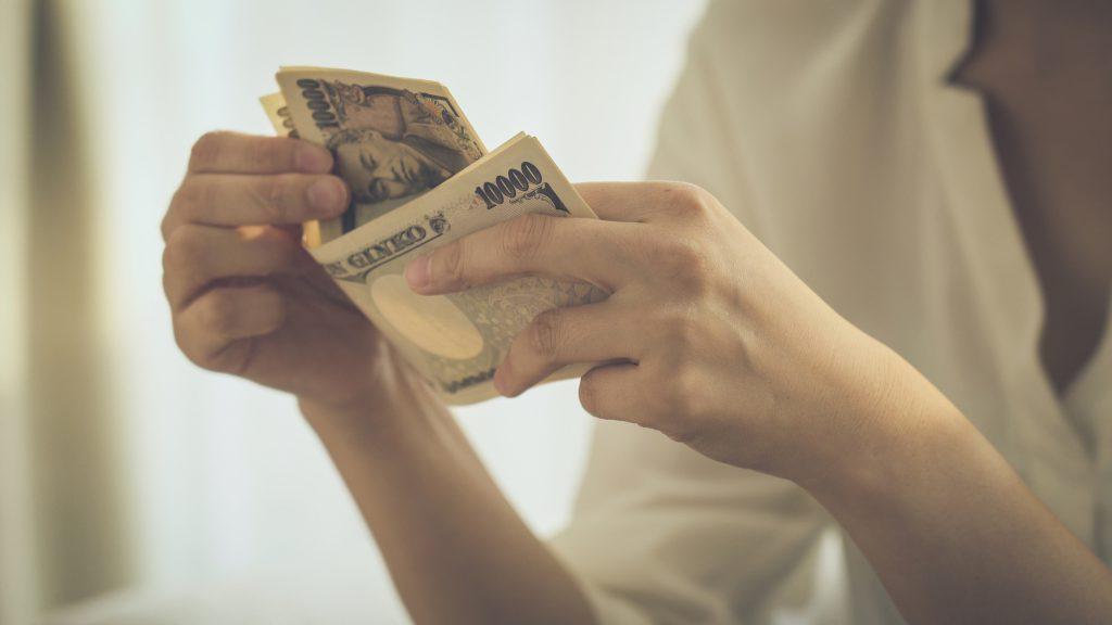 1万円札を数える女性の手