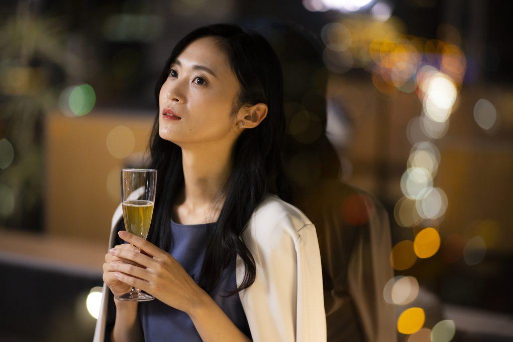 夜景をバックにカクテルを飲む女性