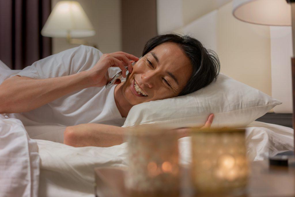 ベッドで電話する男性